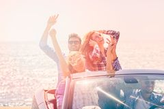Beautiful party friend girls dancing in a car on the beach happy.  Royalty Free Stock Photography
