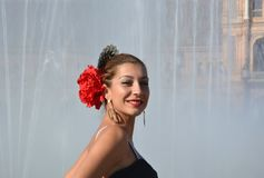 The beautiful and passionate Andalusian woman in front of the fountain, goes to the Feria de Abril in Seville, Spain. The traditional feria de Abril, in Seville royalty free stock photo