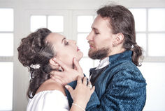Beautiful passionate couple woman and man in medieval clothes. Beautiful passionate couple women and men in medieval clothes in the room Stock Image
