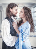 Beautiful passionate couple woman and man in medieval clothes. Beautiful passionate couple women and men in medieval clothes in the room Royalty Free Stock Photography