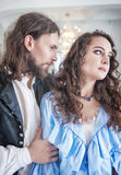 Beautiful passionate couple woman and man in medieval clothes. Beautiful passionate couple women and men in medieval clothes in the room Royalty Free Stock Photos