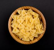Pasta Farfalle in wooden bowl on black background, top view, centered stock photos