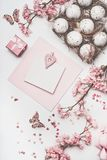 Beautiful pastel pink Easter greeting card mock up with blossom decoration, hearts, eggs in carton box on white desk stock photography