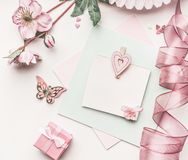 Beautiful pastel pink layout with flowers decoration,ribbon, hearts and card mock up on white desk background, top view, flat lay. Wedding invitation, girls Royalty Free Stock Image