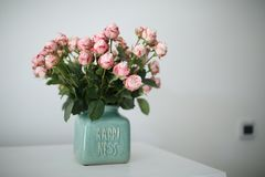 Beautiful pastel pink roses in a shabby chic crackled vase with the word happiness on it stock images