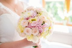 Beautiful pastel wedding bouquet in hands of the bride Stock Photo