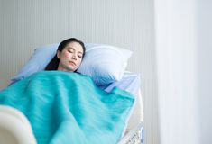 Beautiful patient asian women sleeping under blanket on sickbed at the hospital royalty free stock image