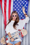 Beautiful patriotic girl. Beautiful girl with a skateboard in front of a flag of the U. S Stock Images