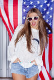 Beautiful patriotic girl. Beautiful girl wearing sunglasses in front of a flag of the United States Royalty Free Stock Photo