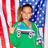 Beautiful patriotic girl. Beautiful girl with a roller skates in front of a flag of the U. S Royalty Free Stock Images