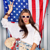 Beautiful patriotic girl. Beautiful girl with a skateboard in front of a flag of the U. S Royalty Free Stock Photo
