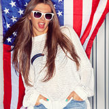 Beautiful patriotic girl. Beautiful girl wearing sunglasses in front of a flag of the United States Royalty Free Stock Images