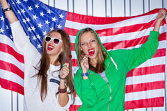 Beautiful patriotic girls with lollipop. Two beautiful girls with red lollipops holding a flag of the USA Stock Images