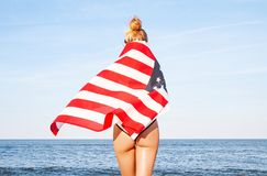 Beautiful patriotic woman with American flag on the beach.  USA Independence day, 4th July. Freedom concept. View from the back royalty free stock image