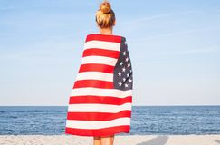 Beautiful patriotic woman with American flag on the beach.  USA Independence day, 4th July. Freedom concept. View from the back royalty free stock photos