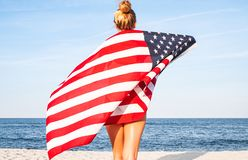 Beautiful patriotic woman with American flag on the beach.  USA Independence day, 4th July. Freedom concept. View from the back stock photography