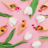 Beautiful pattern with bright sugar candy in waffle cones and white flowers on pink background. Flat lay, top view Stock Photos
