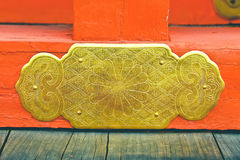 Beautiful patterns on a brass plate fix on red color wood Royalty Free Stock Image