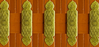 Beautiful patterns on a brass plate fix on red color wood.  Royalty Free Stock Images