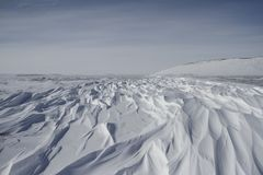 Beautiful patterns of sastrugi, parallel wavelike ridges caused by winds on surface of hard snow. With soft clouds in the sky, near Arviat Nunavut Canada royalty free stock photography