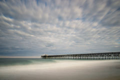 Beautiful ocean pier under an impressive sky and calm seas Royalty Free Stock Image