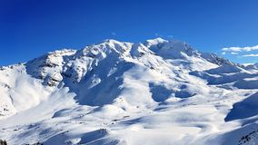 Mountain in snow under blue sky. Beautiful peak mountain in the snow under blue sky Stock Image