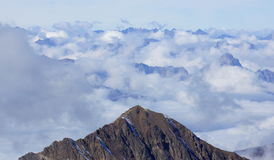 Beautiful peaks in the Alps surrounded by light white clouds Stock Photos