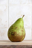 A beautiful pear on a chopping board Royalty Free Stock Image