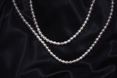 Beautiful pearl necklace on black silk Stock Photo