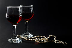 Beautiful Pearl Necklace and Two Glass Cups of Red Wine Isolated on Black Stock Images
