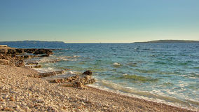Beautiful pebble beach of Mali Losinj. Beach with volcanic rocks and pebbles along the Adriatic sea with islands in the background on Mali Losinj island, Croatia Stock Image