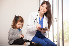 Beautiful pediatrician at work. Portrait of a gorgeous pediatrician loving her job and sitting next to a little girl Stock Images