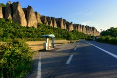Beautiful Penitent rocks in Provence. Road with bus stop near famous Penitent rocks illuminated by evening sun Stock Images