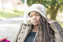 Beautiful pensive african young woman with hat in the park. Royalty Free Stock Photo