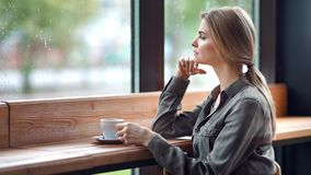 Beautiful pensive blonde unhappy woman looking out of window at rainy autumn day sitting in cafe. Bored attractive girl feeling sadness and loneliness having stock video footage