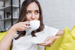 Beautiful pensive brunette girl drinking coffee and looking away. At home royalty free stock image
