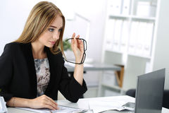 Beautiful pensive businesswoman sitting at her working place Stock Images