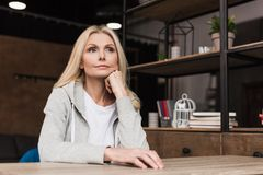 Beautiful pensive middle aged woman. Looking away while sitting at home stock photography