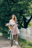 Beautiful pensive woman in dress with retro bicycle with wicker basket full of flowers. At countryside stock image