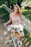 Beautiful pensive woman in dress with retro bicycle with wicker basket full of flowers. At countryside stock photos