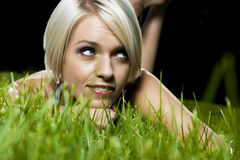Beautiful pensive woman lying on grass Royalty Free Stock Photos