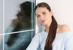 Beautiful pensive woman sitting by the window at home Royalty Free Stock Photo