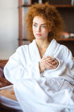Beautiful pensive woman in white bathrobe sitting and relaxing Stock Photos