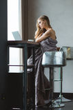 Beautiful pensive  woman wrapped in grey knitted coverlet using laptop Stock Photo