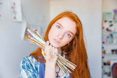 Beautiful pensive young woman painter holding paintbrushes in art studio. Beautiful pensive young woman painter with long red hair holding paintbrushes in art Stock Photography