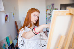 Beautiful pensive young woman painter working in art studio Royalty Free Stock Images