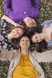 Beautiful people friends lying on the grass smiling Stock Photo