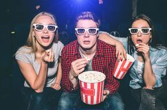 Beautiful people in glasses are looking straight forward. They has opened their mouthes. Each of them has a piece of. Popcorn in their hands. They look excited Royalty Free Stock Photos