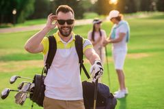 People playing golf. Beautiful people are resting and playing golf, handsome guy in the foreground is looking at camera and smiling Stock Photos