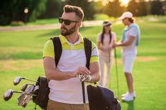 People playing golf. Beautiful people are resting and playing golf, handsome guy in the foreground Stock Photos